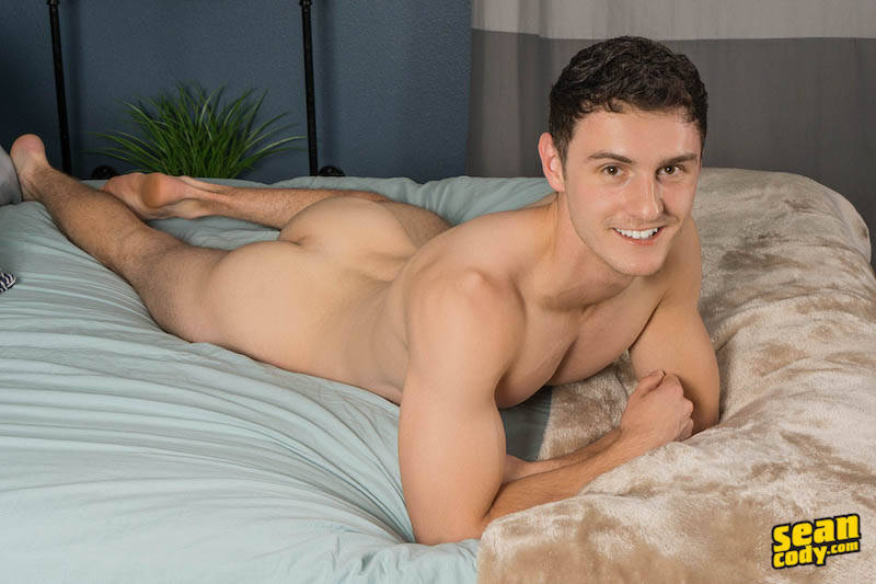 Smiling jock laying naked on a bed with his ass on show