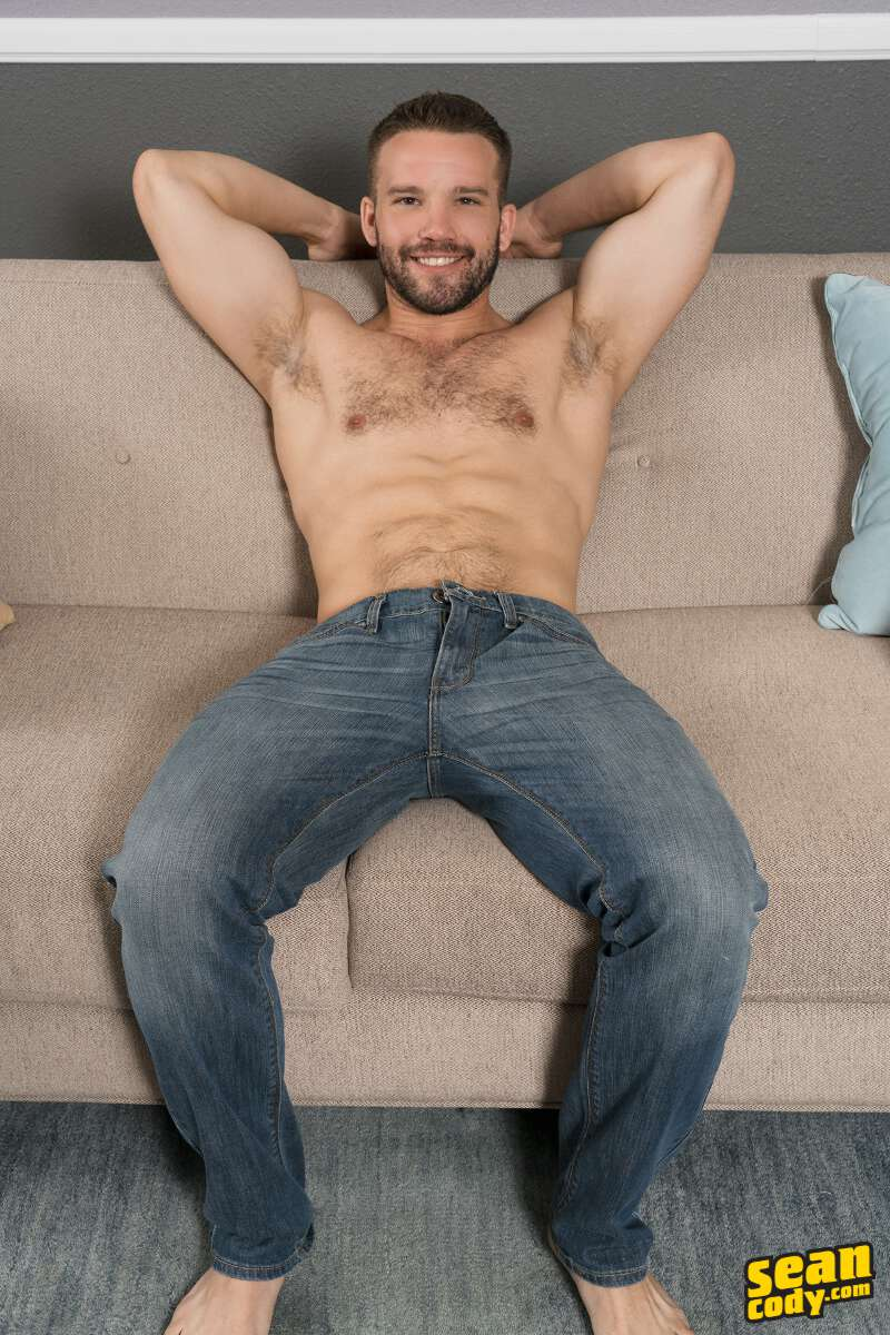 muscled jock shirtless in jeans on a couch