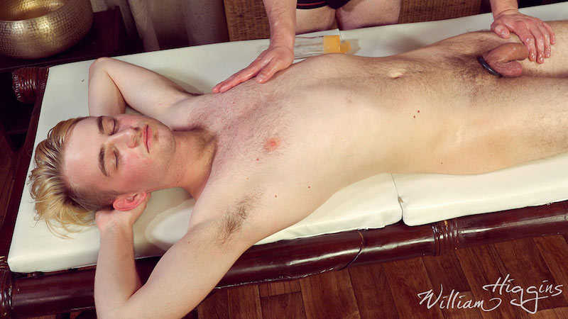 naked twink with a cock ring laying on a massage table